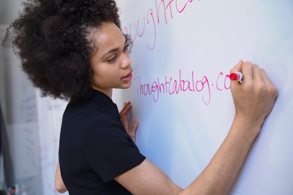 ホワイトボードに書いている女性